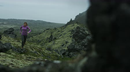 desolado : Panning shot of woman trail running up hill in Iceland