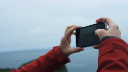 üdítő : over shoulder shot of woman taking photo of seascape in Iceland with cell phone Stock mozgókép