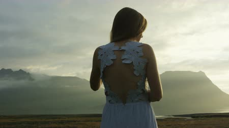 tilt down : panning shot of woman in dress taking in the view in Iceland Stock Footage