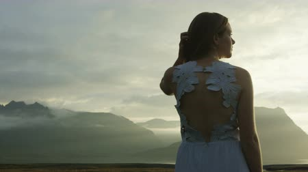 authenticity : panning shot of woman in dress taking in the view in Iceland Stock Footage