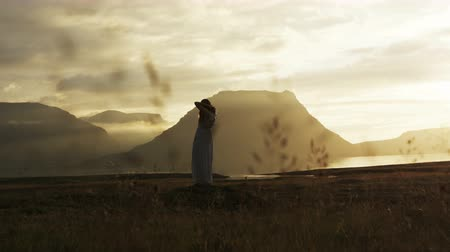 tilt down : panning shot of woman in dress at sunset with cloudy mountains in background at sunset in Iceland