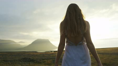 authenticity : woman in dress walking through field at sunset in Iceland Stock Footage