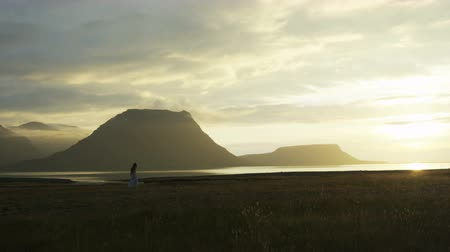 authenticity : panning shot of woman in dress walking near sea at sunset in Iceland