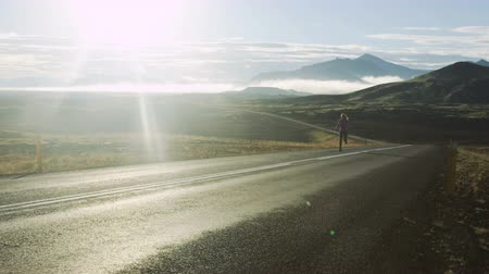 колготки : woman running up road in Iceland with mountains in background