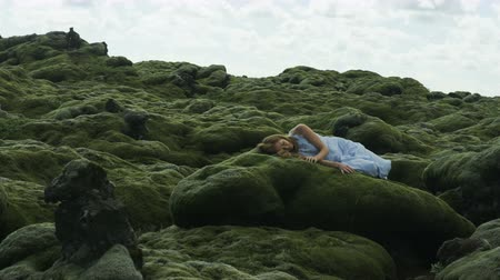 hazugság : Woman laying on moss covered rock in Iceland stares up at the clouds