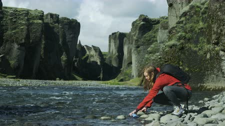 üdítő : Woman hiker stops to fill up water bottle in river while hiking in Iceland Stock mozgókép