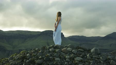ruha : Woman in dress standing in the wind in Iceland with storm coming Stock mozgókép