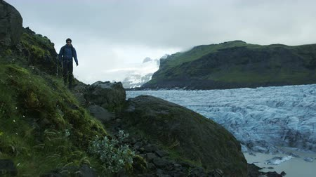 islandia : man hiking near glacier field in Iceland