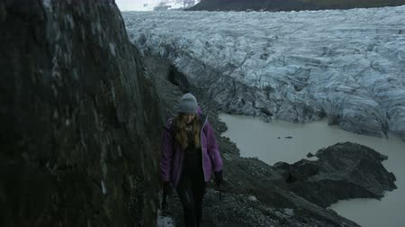 félteke : woman hiking near glacier field in Iceland