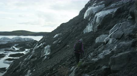 iceberg : woman hiking near glacier field in Iceland
