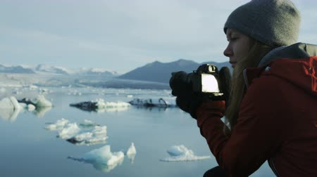 fotoğrafçı : woman taking photos of icebergs in Icelands Jokulsarlon glacial lagoon Stok Video