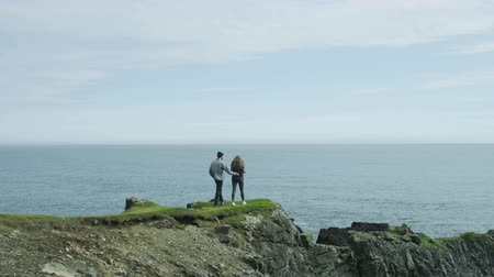 pažba : Couple walks towards edge of ocean cliffs, takes in the view together in Iceland