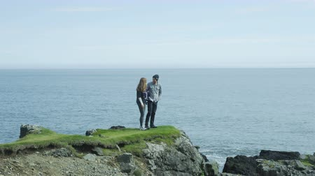 pažba : couple walks out to ocean cliffs, takes in view together