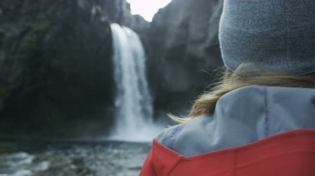 bum : panning shot of woman looking at waterfall Stock Footage