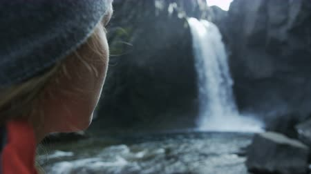 csikk : close up of womans face as she looks at waterfall