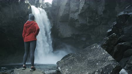 pažba : woman looking at waterfall in Iceland