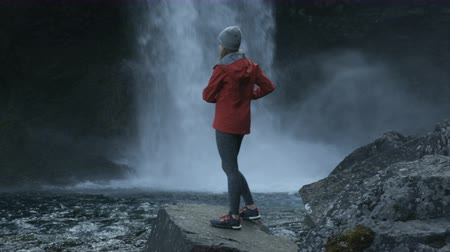 zadnice : woman tourist in Iceland taking photo of waterfall with her cell phone