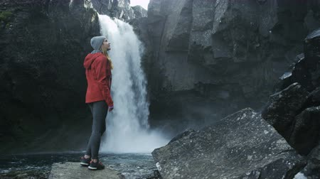 pažba : woman standing on a rock looking at waterfall in Iceland
