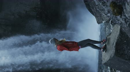 zadnice : vertical shot of woman taking in view next to waterfall in Iceland Dostupné videozáznamy