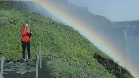 picturesque view : woman taking photos with rainbow in background in Iceland Stock Footage