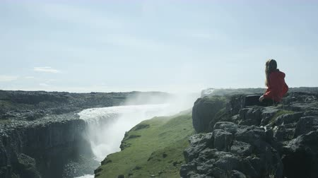 raincoat : woman sitting at edge of cliffs looking at Detifoss waterfall in Iceland