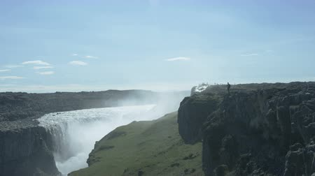 gullfoss : man standing on edge of cliff taking photos of Dettifoss waterfall in Iceland Stock Footage