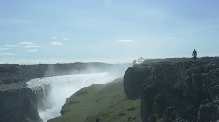 gullfoss : man hiking on cliffs above Dettifoss waterfall in Iceland Stock Footage