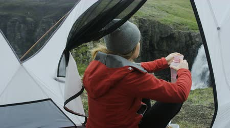 выживание : woman sitting in tent drinking water in the morning Стоковые видеозаписи