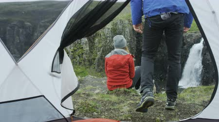 честолюбие : man gets out of tent, sits next to girl to check out view