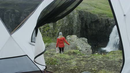 честолюбие : woman walks out of tent towards view of waterfall Стоковые видеозаписи