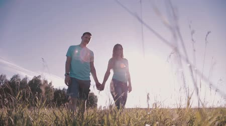 small park : A young couple holding hands and walking on the grass in a meadow in the woods