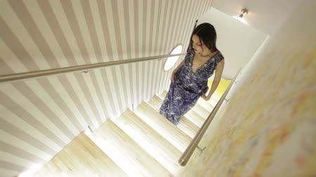 escada : Beautiful Woman In A Dress Is Going Up The Stairs Stock Footage