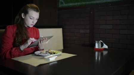 coffe : The girl in the red dress sits at a table in the restaurant and use the digital tablet. Stock Footage