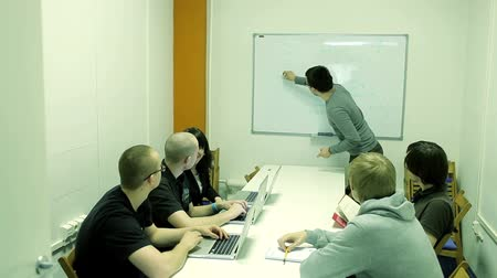 sala de reuniões : Lecturer explains something to a small group with a laptop and draws on the board.