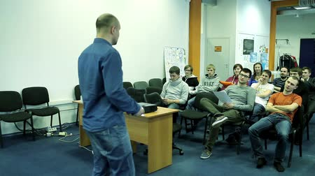 programmers : Man talking with a small group of students in a audience.