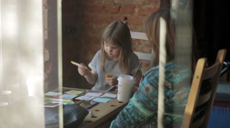 caffe : Little girl draws markers at a table in a cafe Stock Footage