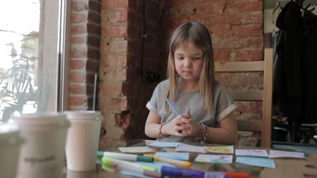 yazarak : Smiling little girl draws with markers at a table in a coffee shop