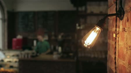 açık kahverengi : Close up of a lamp lights in a cafe. The staff behind the bar in the background Stok Video