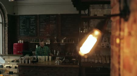 açık kahverengi : Close up of a lamp turned off in a cafe. The staff behind the bar in the background