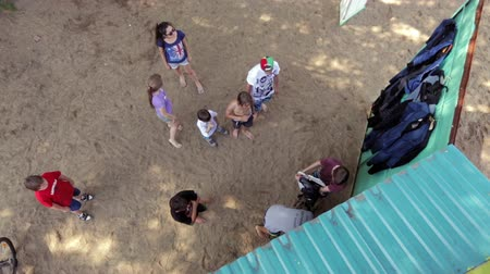 equipamentos esportivos : Young people on the beach coming to the pantry and takes sports equipment, overhead view.