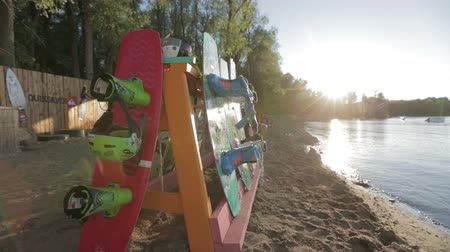 safe workout : Stand with wakeboard on the background of the lake, sunset, trees. Stock Footage