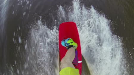 ilk : Shooting from the first person. Wakeboarder rides a reversible winch. Cuts the waves.