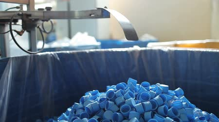 řádek : Many blue plastic bottle caps fall from conveyor to the box.