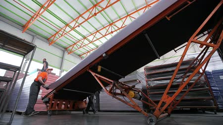 industry : Workers Loaded Polycarbonate Sheets To The Tape