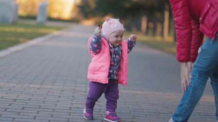 ilk : In autumn park little girl making first steps, her mother helps her. Stok Video