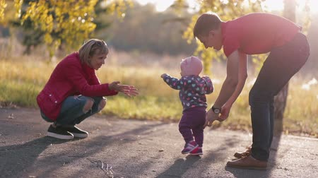 uczenie się : In autumn park child takes its first steps with his family.