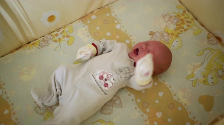 белый : Newborn waving his arms and yawns during sleep. Close-up. Стоковые видеозаписи
