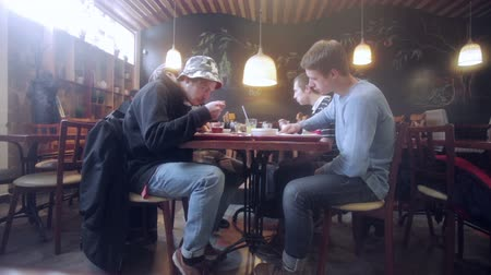 cultura juvenil : Young people eating in a cozy cafe.