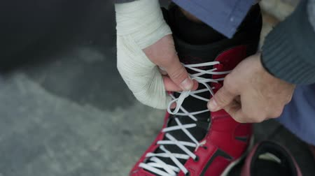bandaż : Snowboarder tying shoelaces. Close-up. Wideo