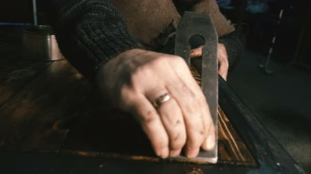 madeira : Carpenter handles the tabletop. Close-up.